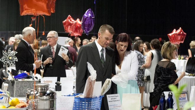 Christina Correll, right, and Jeff Gooding of Visalia browse silent auction items during CASA's 22nd annual dinner auction at the Visalia Convention Center on Friday, May 6, 2016.