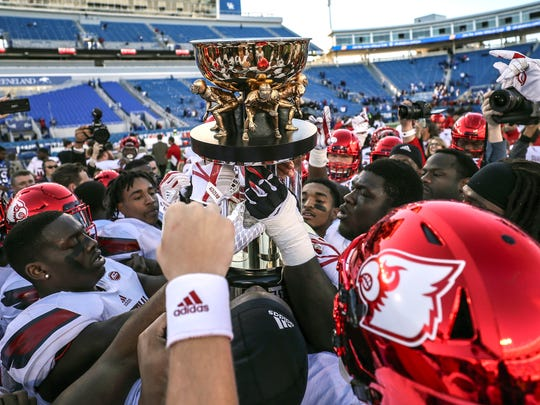 Louisville players celebrate after winning the Governor's Cup with a 44-17 victory over the Wildcats in 2017.