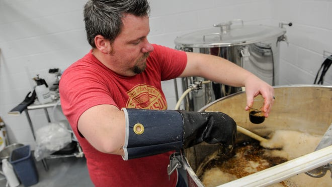 Henderson Brewing Company's head brewer Doug Laramie takes a sample from the mash tun to check the gravity and the pH of a new brew on Wednesday, May 9.