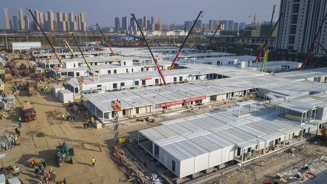 In this photo released by China's Xinhua News Agency, construction workers labor at the Leishenshan Hospital, the second temporary field hospital being built in Wuhan in central China's Hubei Province, on Feb. 4.