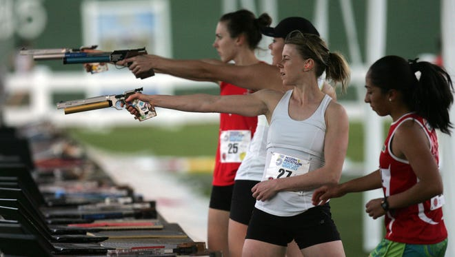 FILE - Competitor shoot during the combine portion of the 2013 women's modern pentathlon World Cup Saturday, February 23, 2013 in Palm Springs.