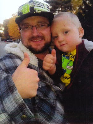 Michael Cope poses for a photograph with his son, little Michael Cope.