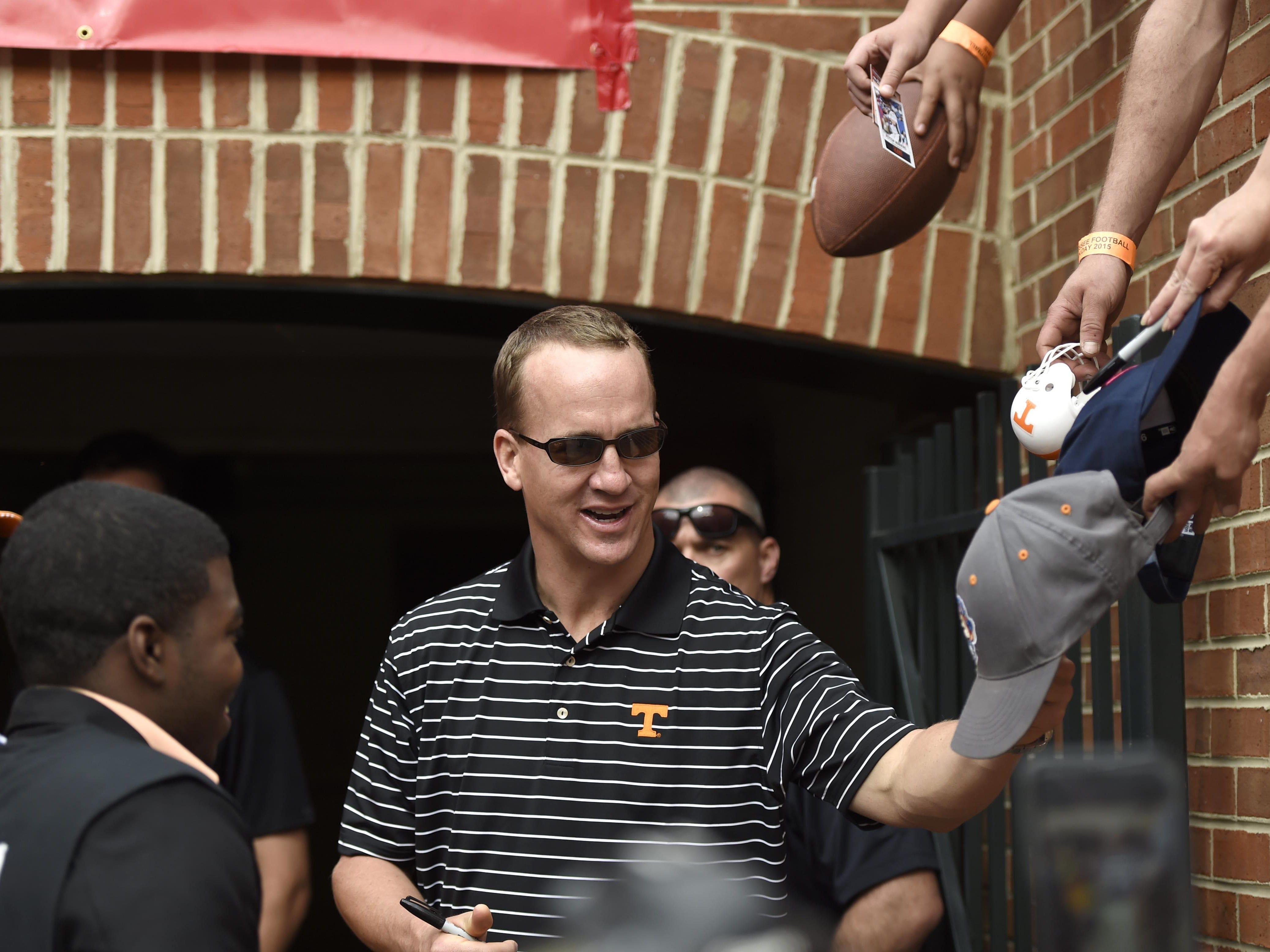Fans hand memorabilia to former Vols quarterback Peyton Manning for autographs during the Orange & White game at Neyland Stadium in April.