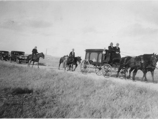 Cowboy artist Charlie Russell's body is carried to high ground in Highland Cemetery by an antique horse-drawn carriage at his funeral in 1926.