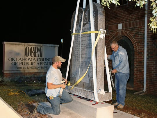Workers place the Ten Commandments monument in its