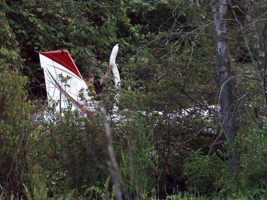 Danbury firefighters set up absorbent booms around a small plane that crashed in a remote swamp off Miry Brook Road near the Danbury Airport July 24, 2014. The pilot was the only person on board and suffered minor injuries.