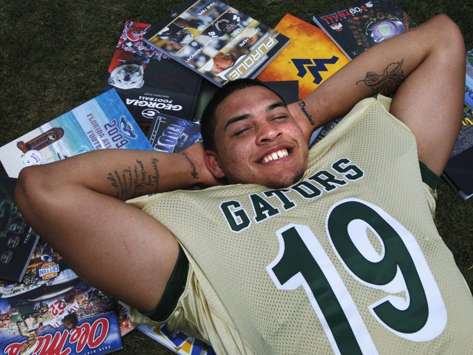Aaron Lynch, a senior defensive end for the Island Coast football team surrounds himself with football brochures from a number the colleges looking to recruit him. Photographed on the Island Coast High School football field, Tuesday,  May 11, 2010.