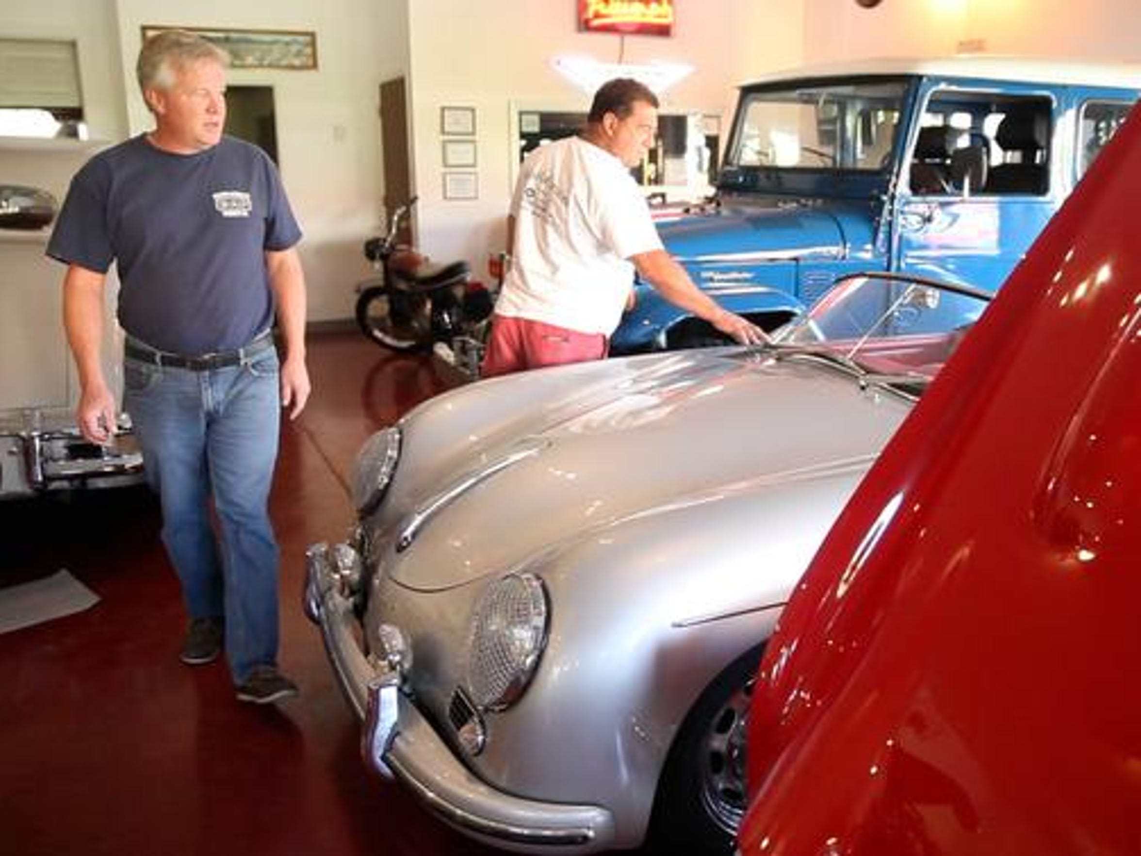Mike Gassman, left, owner of Gassman Automotive Products in Waynesboro, walks a customer through his showroom on Monday, Sept. 14, 2015.