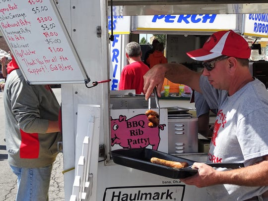 Dale Wagner picks up a couple of bratwurst from the