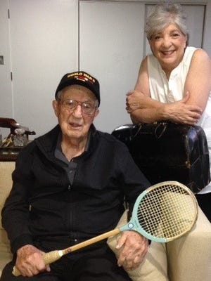 Dr. George Mogill recently celebrated his 100th birthday. For decades he played squash daily. His daughter Jain Lauder is leaning on the medical bag he carried as he made house calls serving patients. He served in the Eighth Medical corps and  proudly wears his World War II baseball cap.