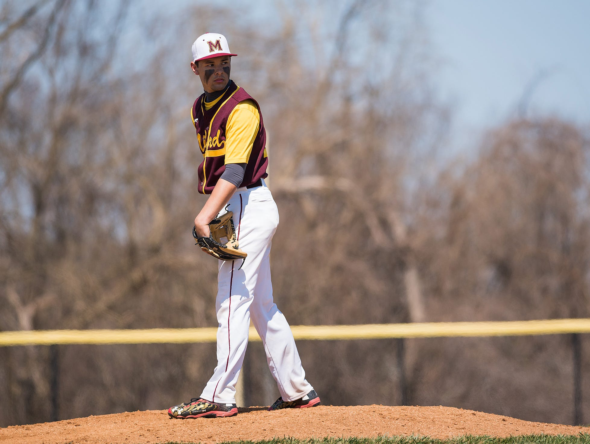 Abraham Mow of Milford looks to first base from the mound.