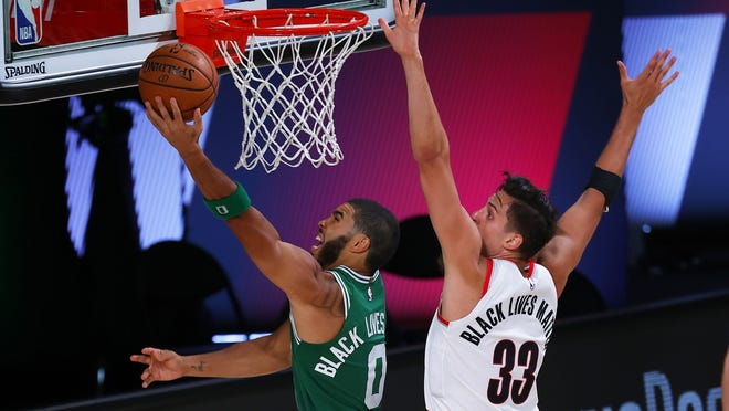 Boston's Jayson Tatum goes up to shoot against Portland's Zach Collins during Sunday's game.
