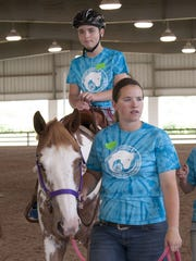 Horse and Pony Project member Carmen Roeming leads a horse at the Winnebago County 4-H Horse and Pony Autism Ride in July 2015. This year's event will be held Sunday at the Winnebago County Fairgrounds.