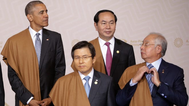 Malaysia's Prime Minister Najib Razak arranges his tie as he waits with President Obama, South Korea Prime Minister Hwang Kyo-ahn and Vietnam's President Tran Dai Quang, Asia Pacific Economic Cooperation summit, Lima, Peru, Nov. 20, 2016.