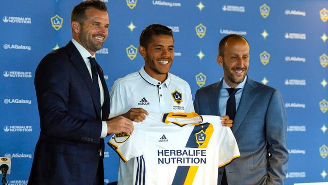 The L.A. Galaxy's new player Jonathan dos Santos holds up a  jersey with president Chris Klein, (left) and general manager Pete Vagenas during a press conference in Carson, Calif.