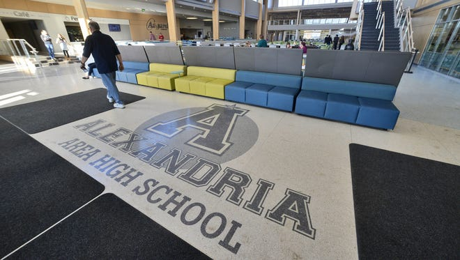 """A custodian walks in February through the Aagard Commons at the heart of the new Alexandria Area High School in Alexandria. It features flexible seating areas and is centrally located to both the gymnasium and auditorium. Superintendent Julie Critz says the new school, which opened last year, has been an """"incredible, unbelievable magnet"""" for the community."""