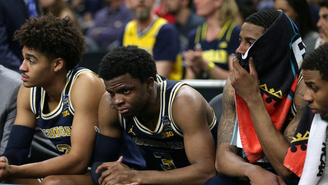 Left to right: Michigan's Jordan Poole, Zavier Simpson and Charles Matthews watch the closing seconds of the 79-62 loss to Villanova in the national championship game Monday, April 2, 2018, at the Alamodome in San Antonio.