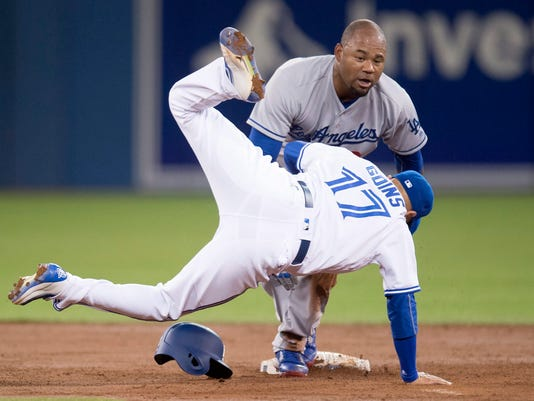 Toronto Blue Jays short stop Ryan Goins tumbles after tagging out Los Angeles Dodgers Carl Crawford as he tried to steal second base during third inning inter-league action in Toronto on Friday, May 6, 2016. (Frank Gunn/The Canadian Press via AP)