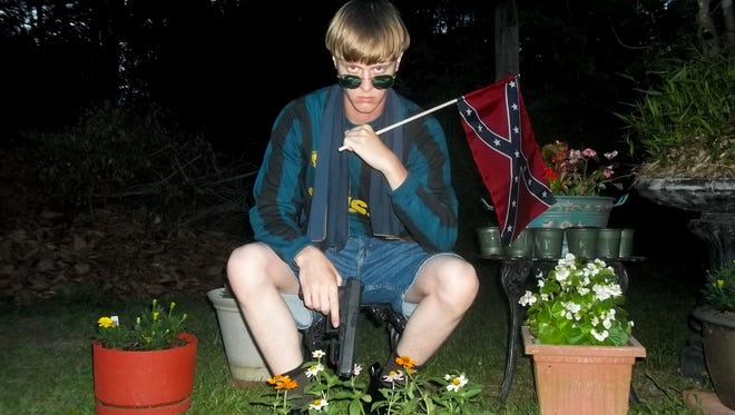 This undated image that appeared on Lastrhodesian.com, a website being investigated by the FBI in connection with Charleston, S.C., shooting suspect Dylann Roof, shows Roof posing for a photo while holding a Confederate flag. The website surfaced online Saturday, June 20, 2015, and also contained a hate-filled 2,500-word essay that talks about white supremacy and concludes by saying the author alone will need to take action.
