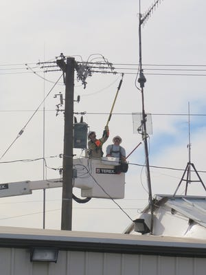 Crews with the St. George Energy Services Department work to repair damaged equipment atop a power poll on north Bluff Street in St. George on Thursday, Dec. 10, 2015.