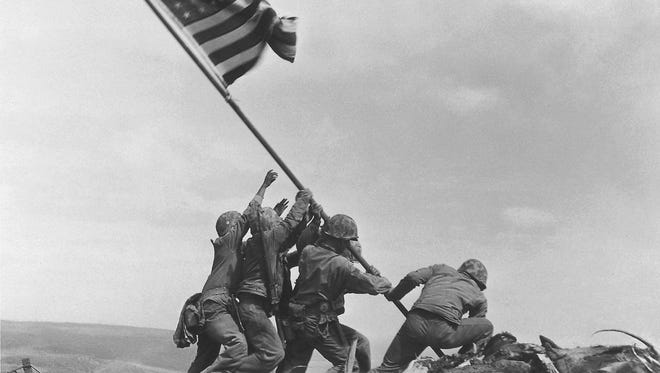 In this Feb 23, 1945, photo taken by Joe Rosenthal, U.S. Marines of the 28th Regiment, 5th Division, raise the American flag atop Mount Suribachi, Iwo Jima, Japan. The Marine Corps acknowledged Thursday, June 23, it had misidentified one of the six men in the photo.