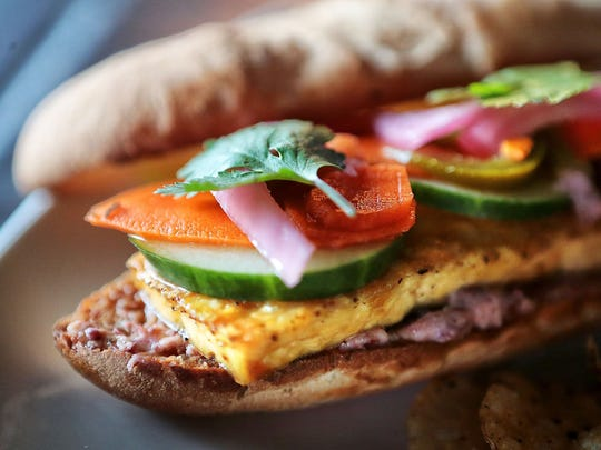 Octavia Young, head chef at the Midtown Crossing Grill makes Bianca's Bahn Mi sandwich with red bean hummus, marinated tofu, pickled onions & carrots, jalapenos, cilantro, cucumber, and sweet chili vinaigrette on a sourdough baguette.
