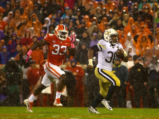 Georgia Tech Yellow Jackets running back KirVonte Benson (30) carries the ball while being defended by Clemson Tigers linebacker J.D. Davis (33) during the first half at Clemson Memorial Stadium.