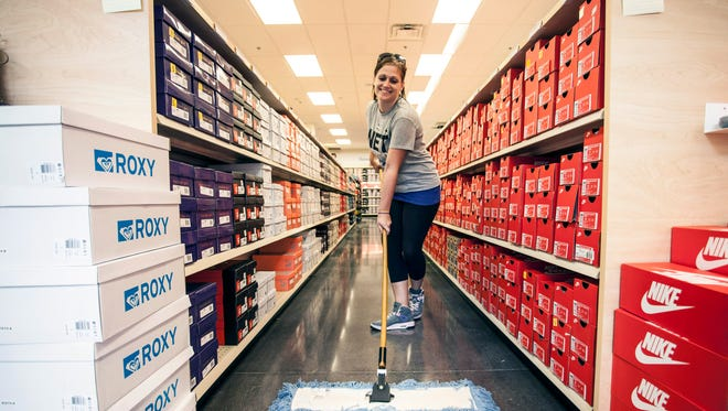 Brittany Profumo sweeps one of the long, long aisles of the Famous Footwear outlet.