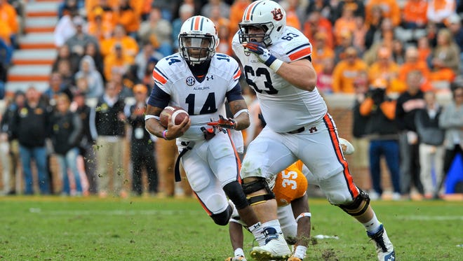 Auburn Tigers offensive linesman Alex Kozan (63) gets set to block for Auburn quarterback Nick Marshall. Kozan has been named to the Outland Award watch list.
