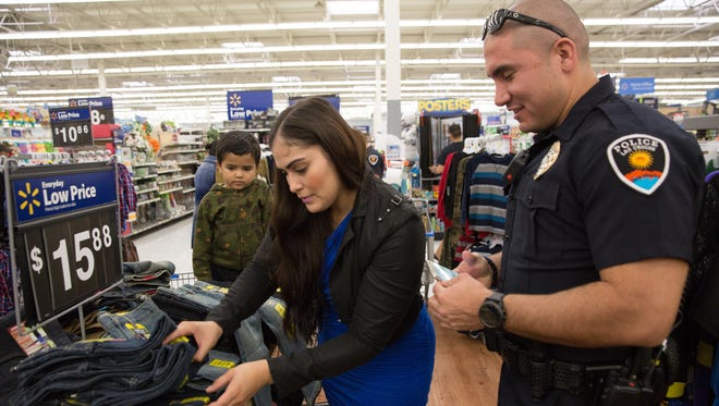 Officer Gil Mora, with the Las Cruces Police Department, keeps track of the clothing items Monica Meraz picks out for her son Alejandro Meraz, 3, during the annual Shop with a Cop event Saturday, Dec. 17, 2016. The participating families were allotted $100 to spend on clothes and toys at the Wal-Mart on Valley Drive.