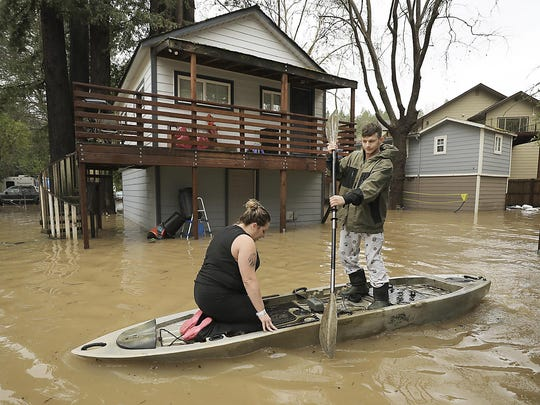 Residents of Sycamore Court flooded by Armstrong Creek, who declined to give their names, paddle out of high water from their apartment in Guerneville, Calif., Feb. 14, 2019. Waves of heavy rain pounded California on Thursday, trapping people in floodwaters, washing away a mountain highway, triggering a mudslide that destroyed homes and forcing residents to flee communities scorched by wildfires last year.