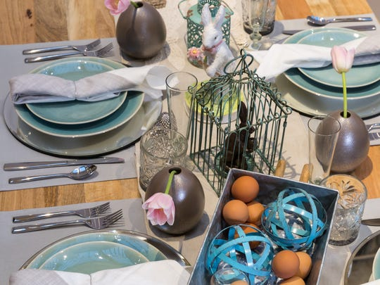 The focal point for this table is the turquoise metal birdhouse and modern metal spheres; it has dishes that are layered atop gray place mats and mirrored chargers.