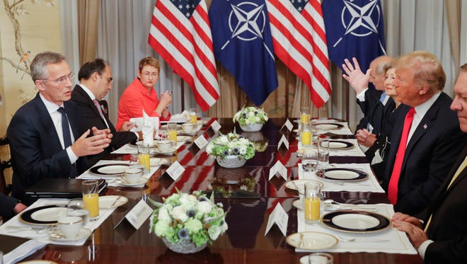 President Donald Trump and NATO Secretary General Jens Stoltenberg both gesture during their bilateral breakfast Wednesday in Brussels.