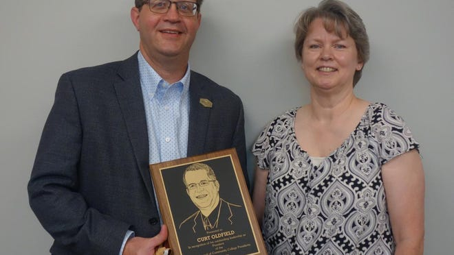 Spoon River College President Curt Oldfield holds a plaque recognizing his work as Chair of the Illinois Council of Community College Presidents this past year.