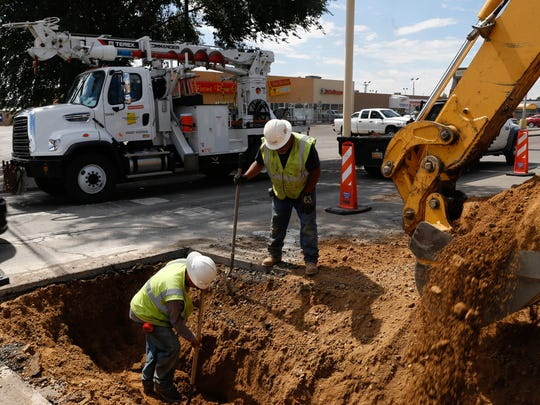 TRC Construction workers install electric lines Sept. 21 at the intersection of North Hutton Avenue and East 20th Street in Farmington.