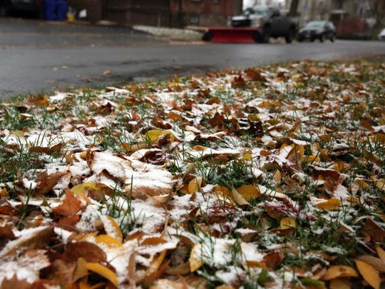 Snow just begins to cover leaves in Rochester on Sunday during the first snowstorm of fall.
