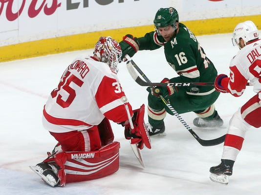 Detroit Red Wings goalie Jimmy Howard, left, stops a shot by Minnesota Wild's Jason Zucker, right, in the first period of an NHL hockey game Sunday, March 4, 2018, in St. Paul, Minn. (AP Photo/Jim Mone)