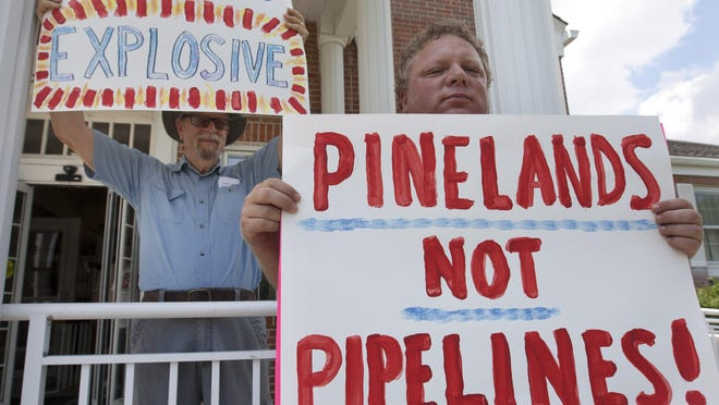 Bill Reitter (left), Glassboro, and Paul Williams, Toms River protested a proposed New Jersey Natural Gas pipeline at a meeting in Manchester Tuesday.