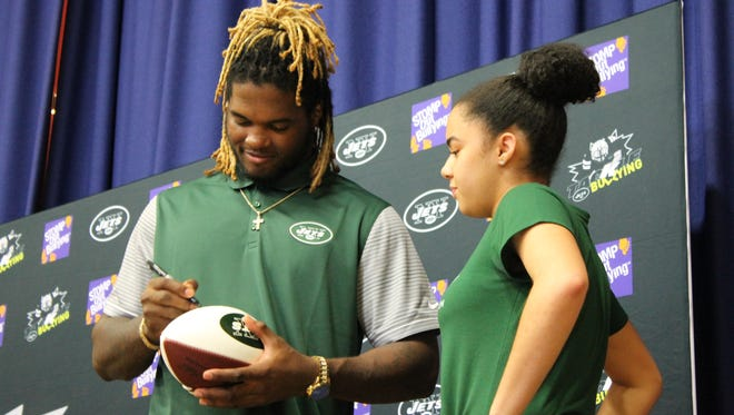 Jets linebacker Lorenzo Mauldin signs a football for a Belleville Middle School student during a presentation on reducing bullying at the middle school on Friday, May 19, 2017.