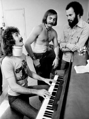 Don Sumner, left, Sean Nielsen and Tim Beaty of The Voice, a pop-rock-gospel trio, warm up before their performance at The Villa at 1711 Hayes St. in Nashville on March 1, 1975. They are still recovering from their injuries when their van veered off the highway and rolled down an embankment a month before.