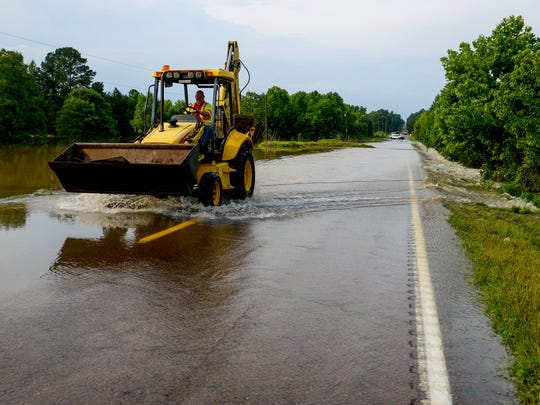 A worker drives back up Highway 18 in the backhoe used to clear the road of fallen trees in the morning hours after flash floods swept through low lands and creek beds at Highway 18 in Medon, Tenn., Monday, July 16, 2018.