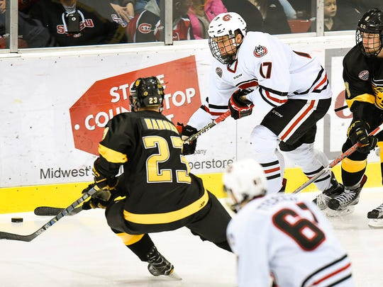 St. Cloud State's Jacob Benson, 17, takes the puck past Colorado College's Matt Hansen, 23, and Colorado College's Luc Gerdes during the first period Saturday, March 4, at the Herb Brooks National Hockey Center.