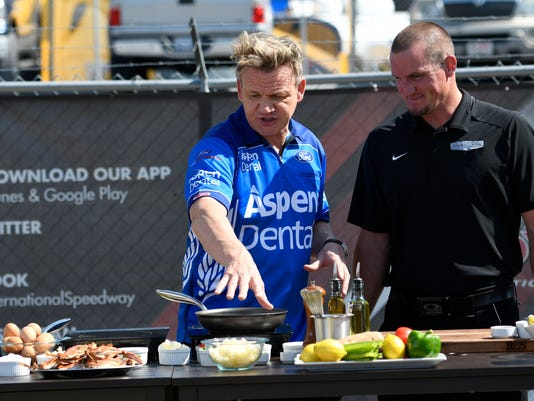 """British celebrity chef Gordon Ramsay, left, films a segment of his show """"The F word"""" before the NASCAR Cup series auto race, Sunday, June 4, 2017, at Dover International Speedway in Dover, Del. At right is tire changer Eric Maycroft. (AP Photo/Nick Wass)"""