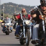 Motorcyclists ride down a street in Sturgis, S.D., for the opening day of the 2014 rally.