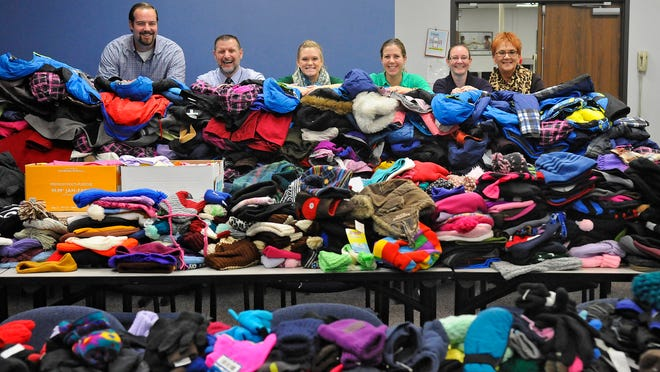 Times Media Employees stand surrounded by a portion of winter wear and bankets collected during Make a Difference Day events Oct. 25.