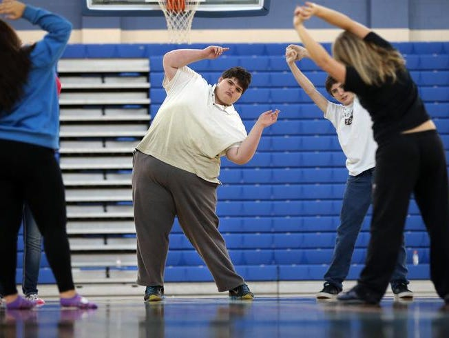 Eric Ekis, a freshman at Franklin High School in Franklin IN, started high school weighing in at around 500 lbs. Thanks to the help of teachers Don Wettrick and Leslie Groce he has started to exercise more and has started better eating habits. Here Eric,middle, begins the day by stretching with his classmates.
