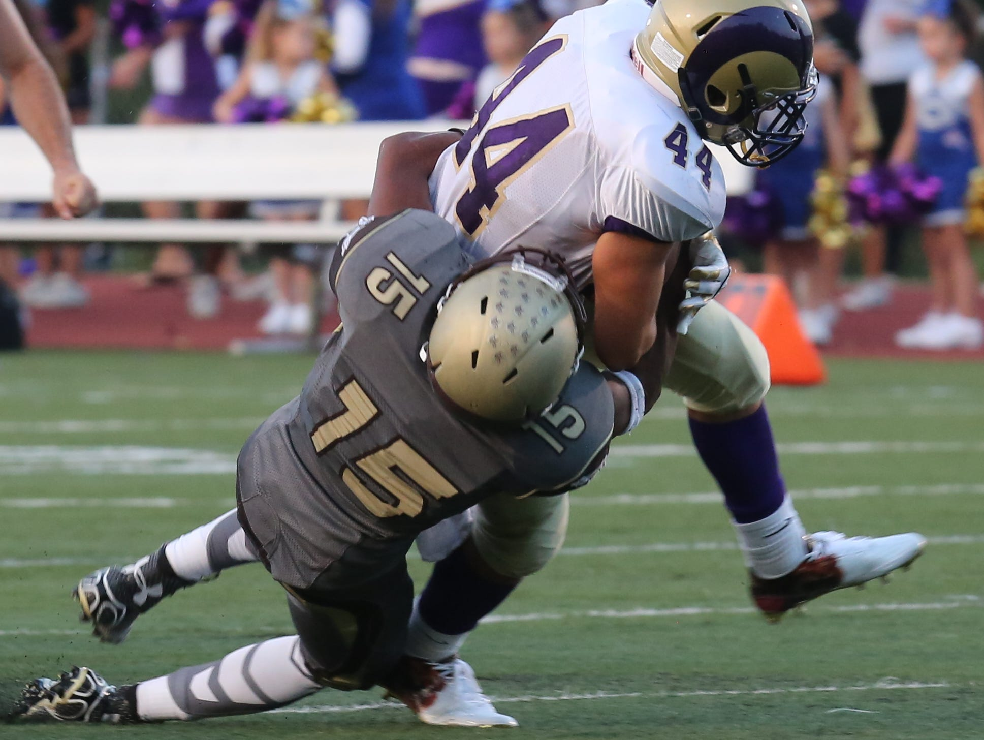 Clarkstown South's August St. Louis (15) tackles Clarkstown North's Michael Porco (44) during game action at Clarkstown South High School in West Nyack Sept. 4, 2015.