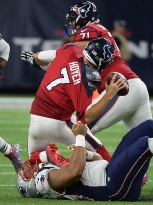 Houston Texans quarterback Brian Hoyer (7) is sacked by New England Patriots defensive end Akiem Hicks on Sunday,  Dec. 13, 2015, in Houston.