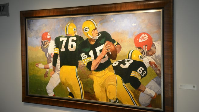 Bart Starr drops back to pass during Super Bowl I in this painting that is among more than 500 pieces of art on display at Lambeau Field.