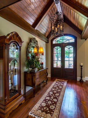 A cathedral wood-stained ceiling greets guests upon arrival while modern chandeliers hang throughout the home.